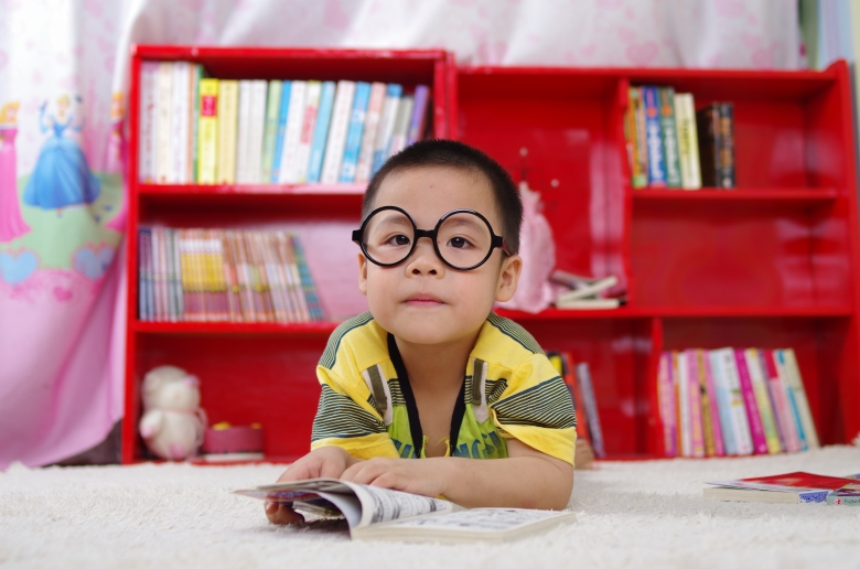 child with sunglasses and bookcase